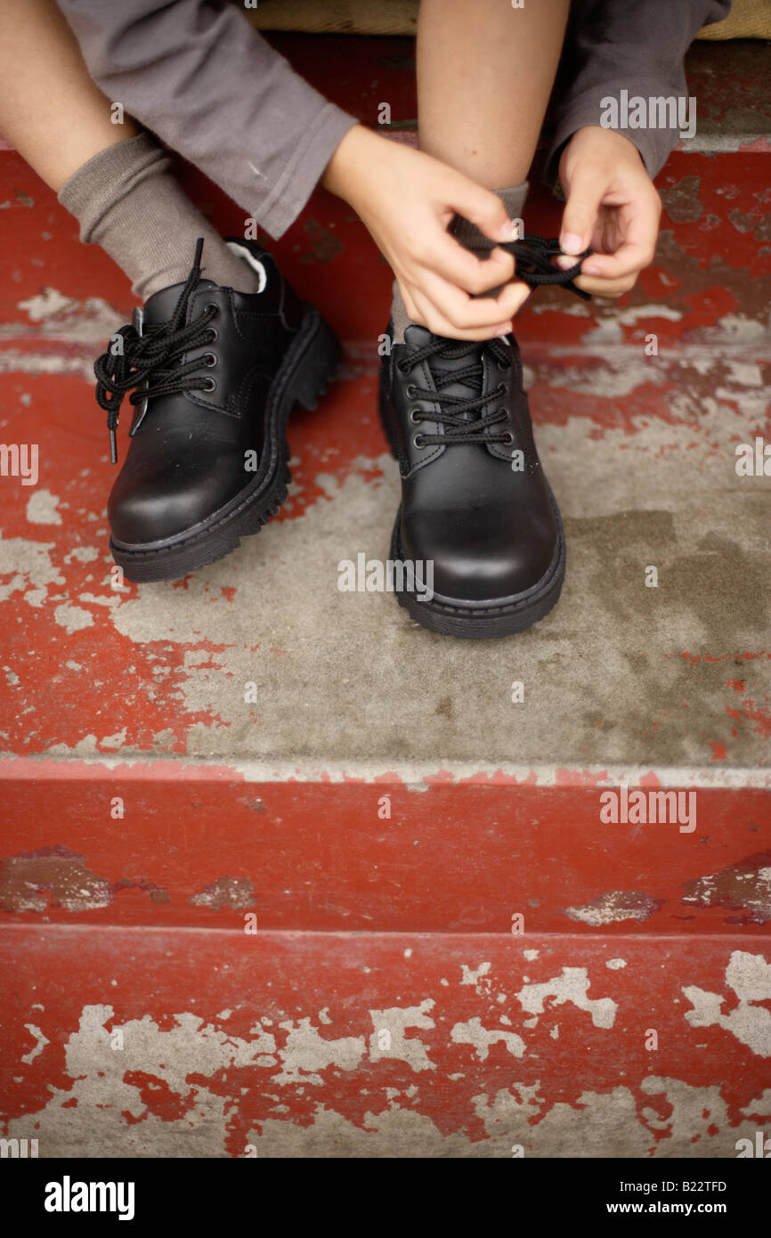 Six year old boy tries to tie laces on his new shoes - Stock Image