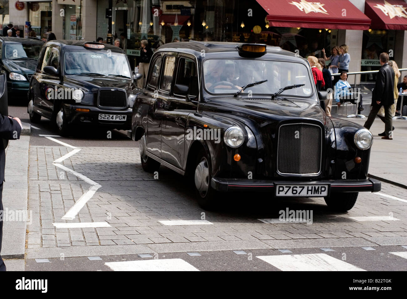 Taxis queue at a zebra crossing in central London. The black cab or hackney carriage is a well known site in London. - Stock Image