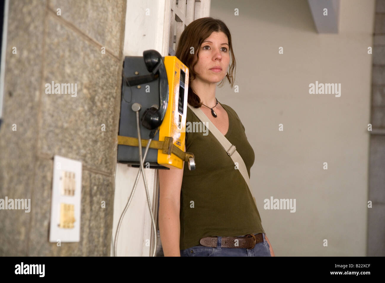 A woman waits by a payphone. - Stock Image