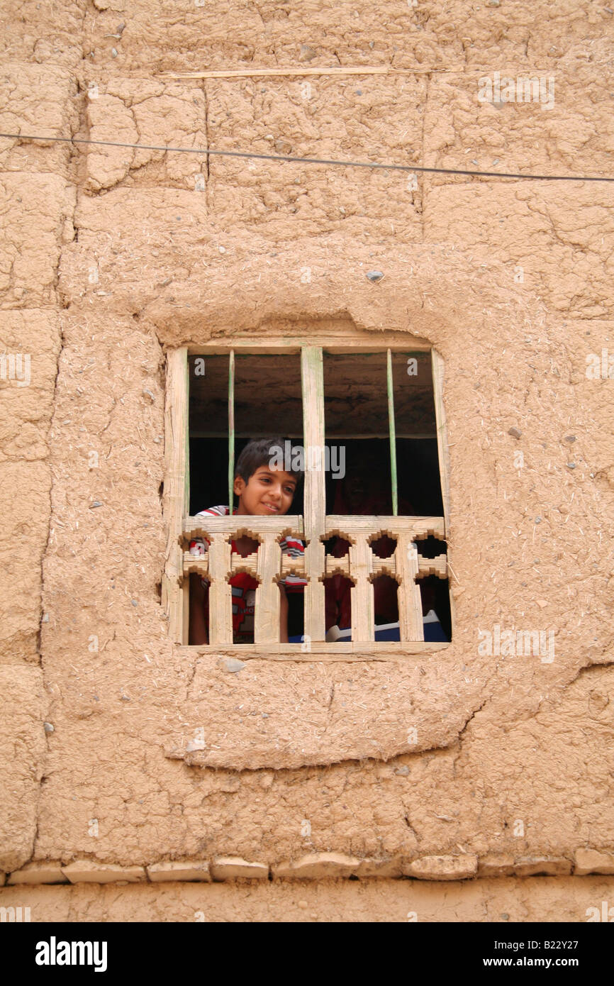 Boy looks out of a window Al Hamra Sultanate of Oman - Stock Image