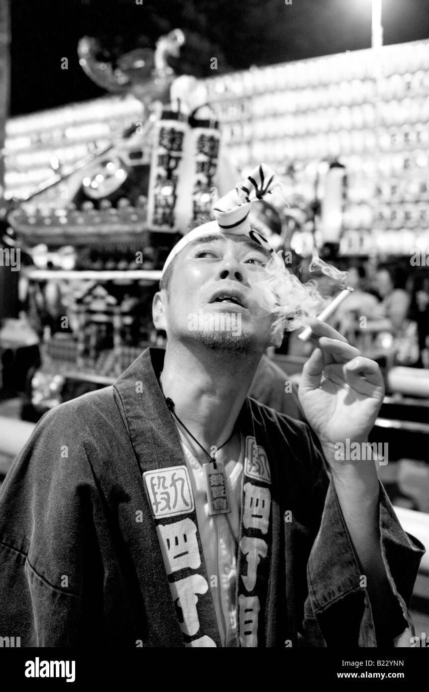 Japanese man in traditional costume smoking a cigarette at the Mitama Festival in Tokyo Japan - Stock Image