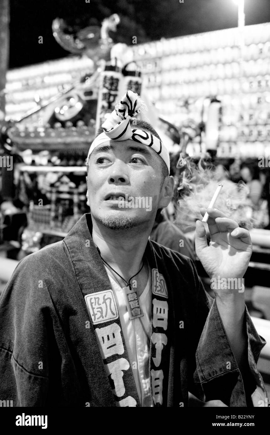 Japanese man in traditional costume smoking a cigarette at the Mitama Festival (Matsuri) in Tokyo, Japan - Stock Image