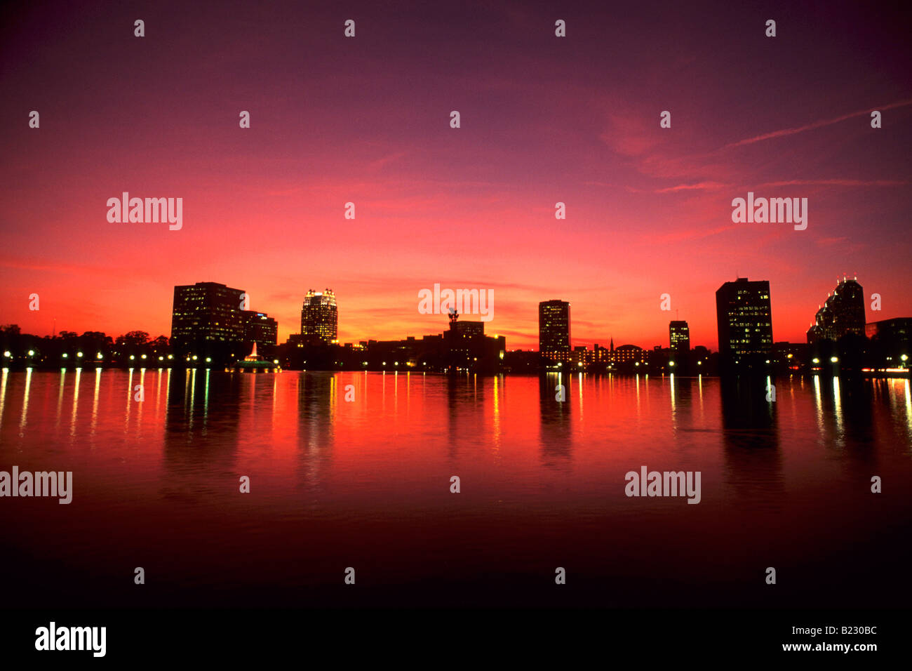 Reflection of buildings in water at dusk, Lake Eola, Orlando, Orange County, Florida, USA - Stock Image