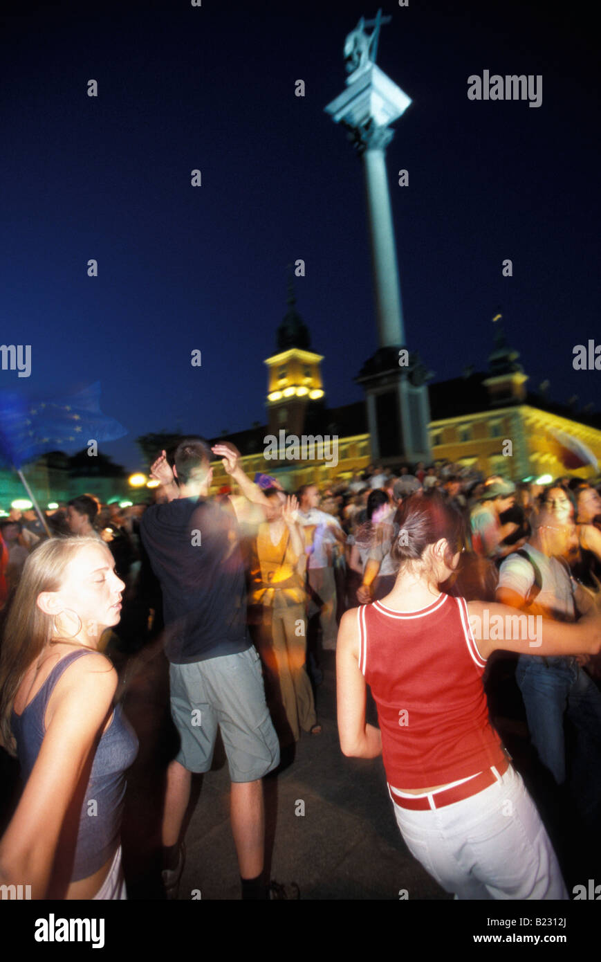 Young people dancing in a square in the Old Town with the Royal Palace and Sigismund Statue in the background Warsaw Stock Photo