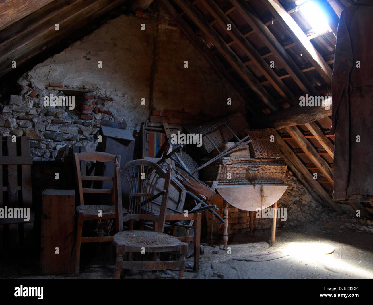 VERY DUSTY ATTIC WITH OLD RELICS AND ANTIQUE FURNITURE IN A FRENCH HOUSE