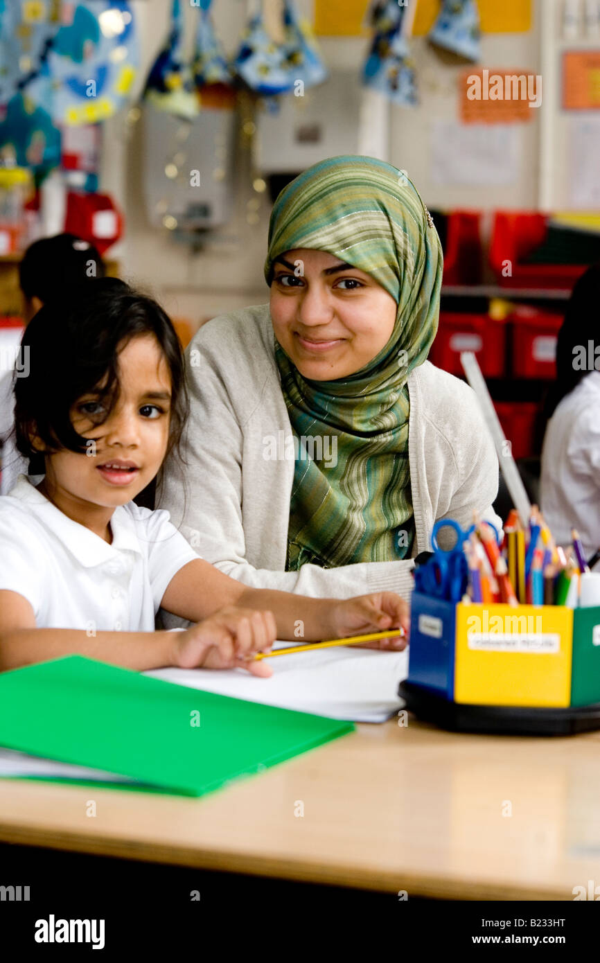 Young Muslim teacher over looks a child learning - Stock Image