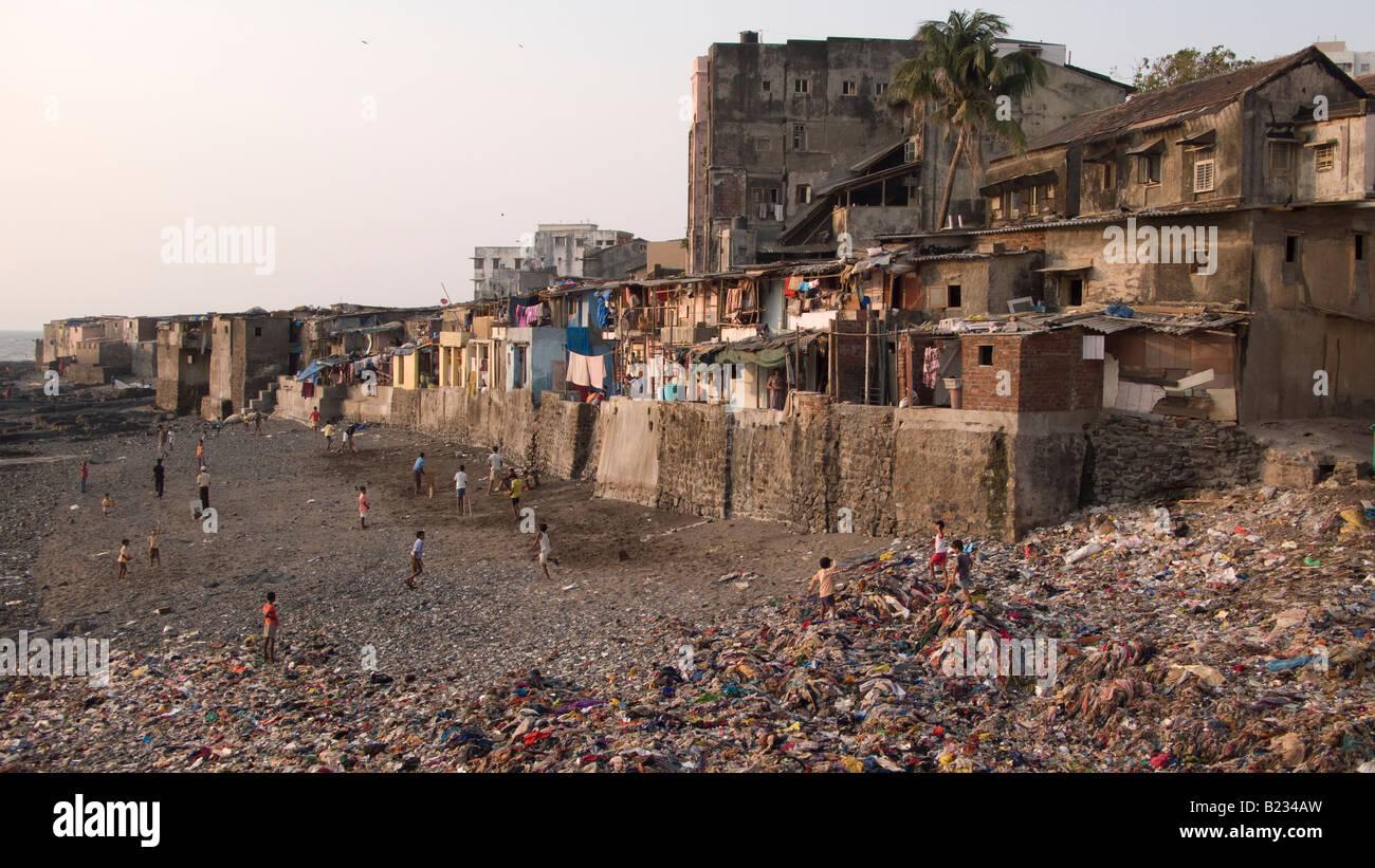 Children playing cricket on a rubbish dump beach in the Teen Batti area of Mumbai India - Stock Image