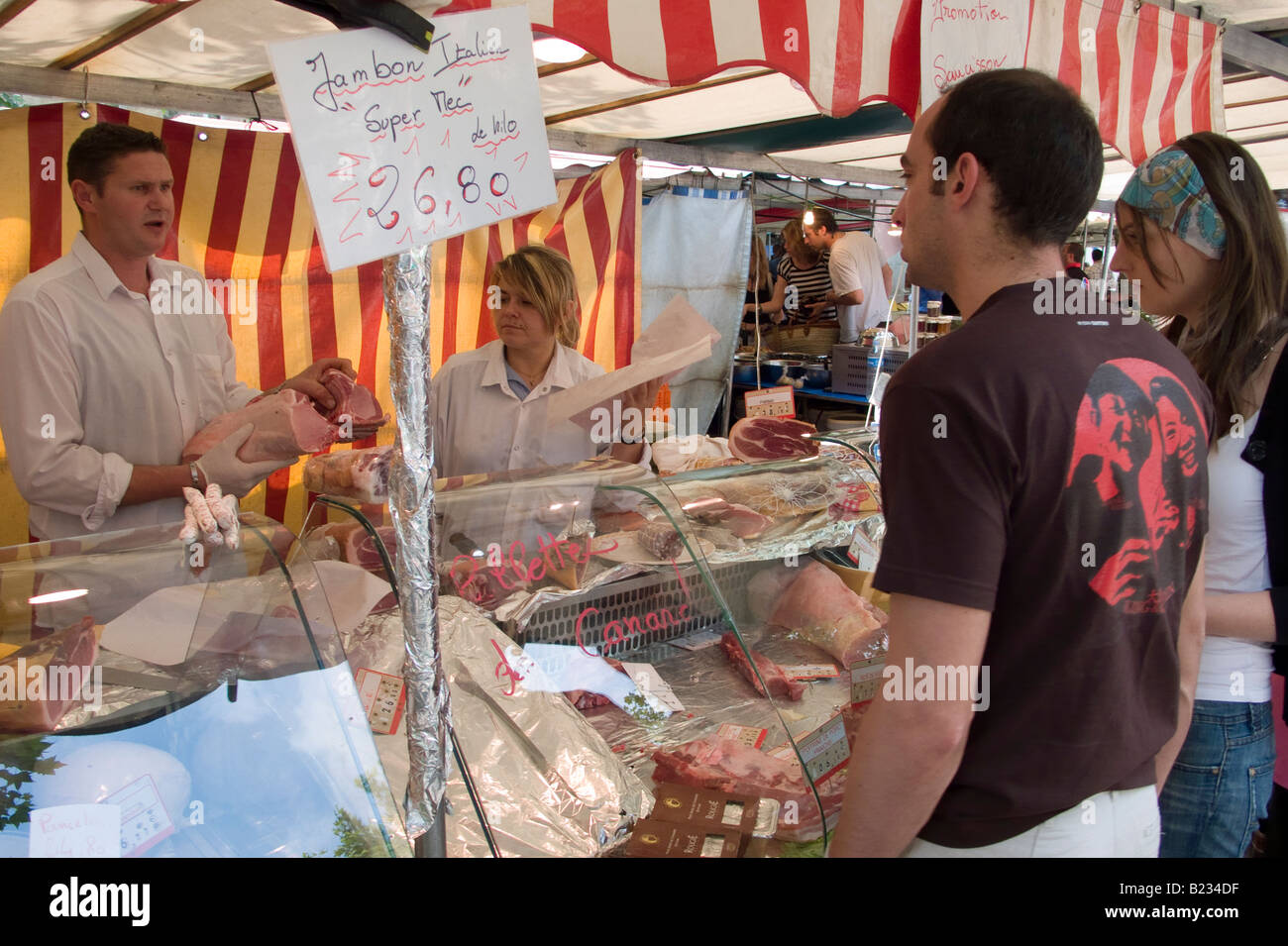Couple buying food from a butcher's stall at a food market in central Paris Stock Photo