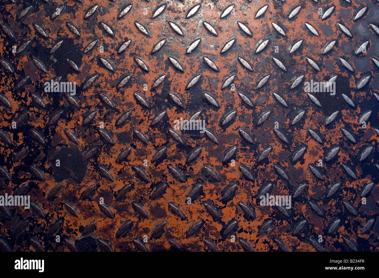 Metal patterened cover with orange paint on street - Stock Image