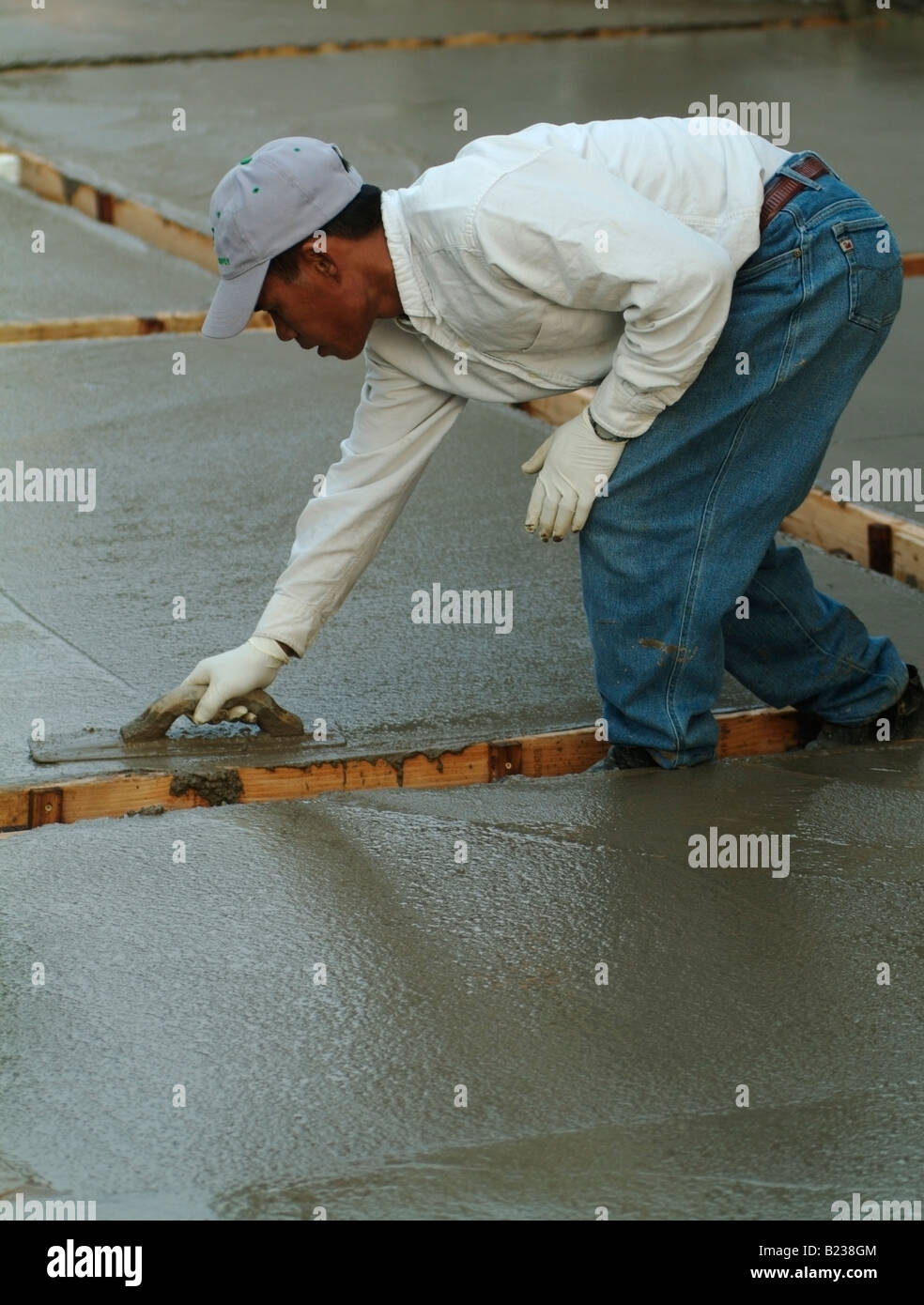 Workman leveling wet concrete with a Darby during construction of a patio in the backyard of a private home in California - Stock Image