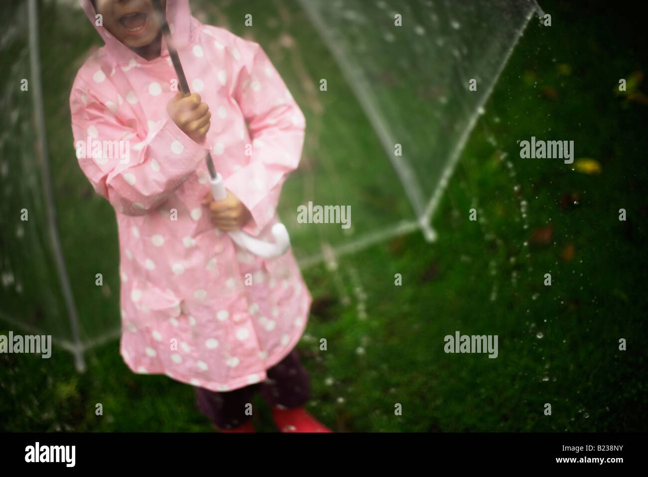 Five year old girl stands in garden with umbrella on a rainy day - Stock Image