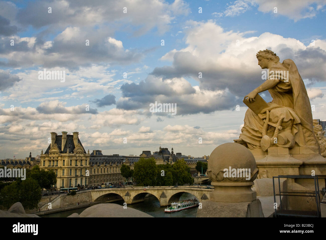 Statue on roof of Musee D'Orsay with dramatic sky background and elevated view of sightseeing boat on the river Seine by famous art Museum the Louvre Stock Photo