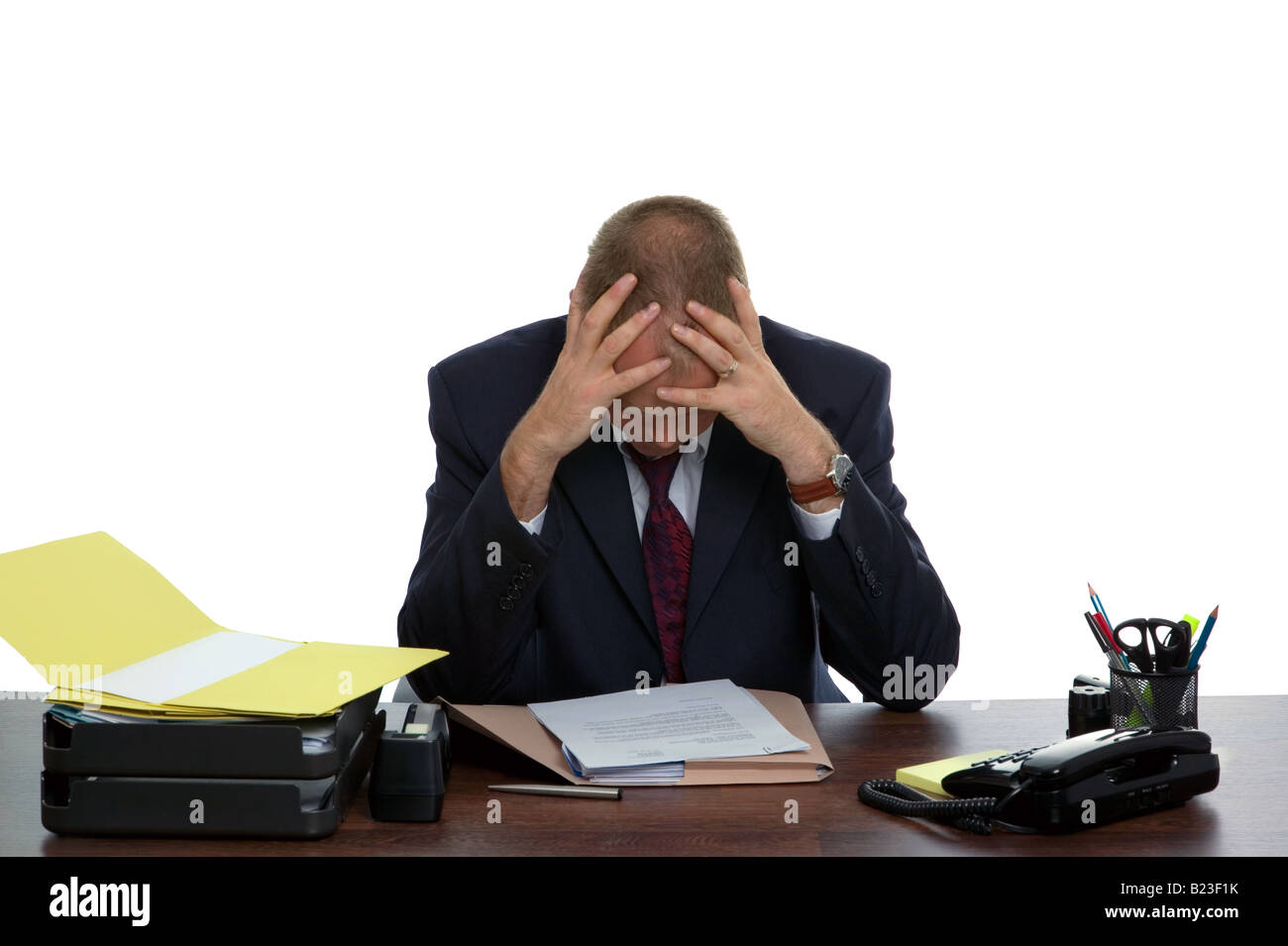 Businessman sat at his desk with hands on his head looking at some paperwork bored with his mundane job - Stock Image