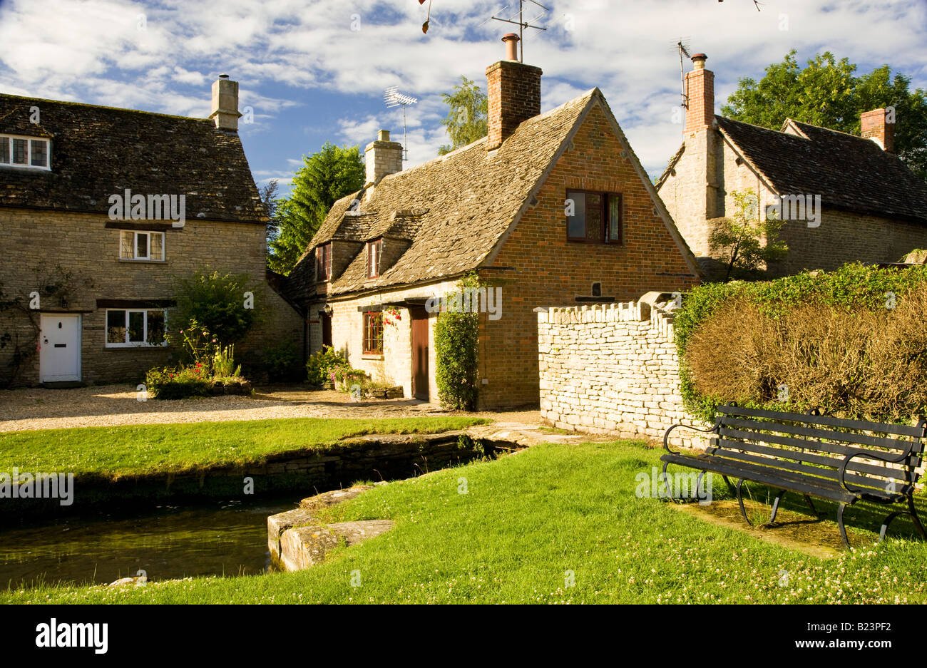 Cotswold stone country village houses by millstream in Church Walk, Ashton Keynes, Wiltshire, England, UK - Stock Image
