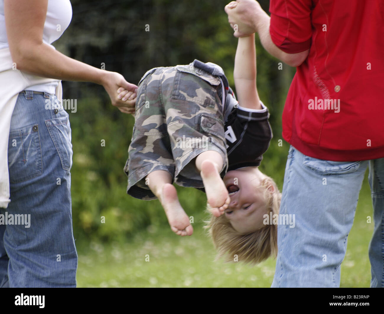 Little boy being spun around in the air by his parents Stock Photo