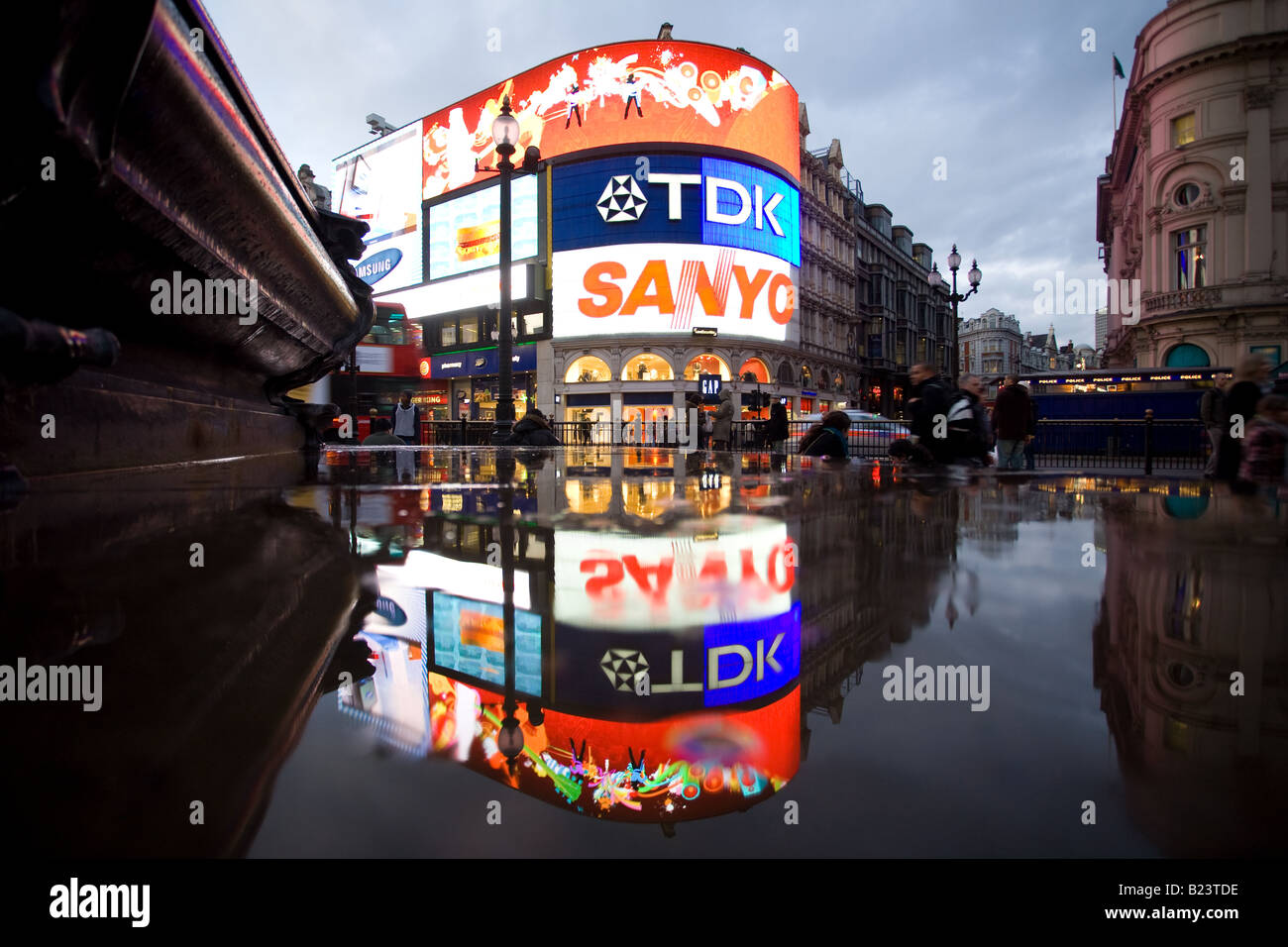 Buildings reflect in the puddles after the rain at Piccadilly Circus. - Stock Image