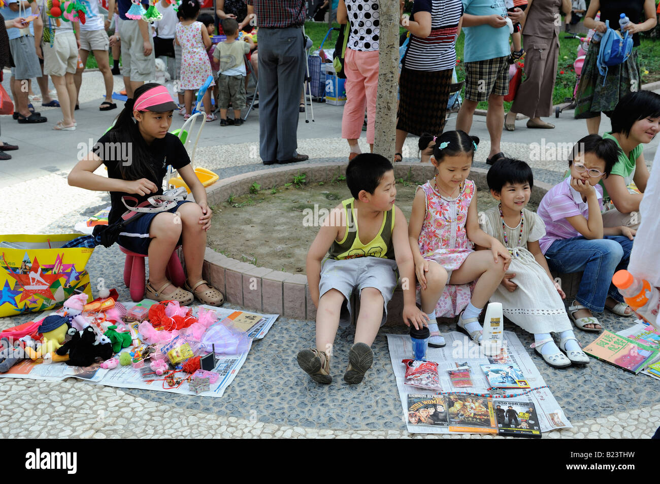 Teenages sell uesd goods at flea market on Sunday in a community in Beijing, China. 13-Jul-2008 - Stock Image