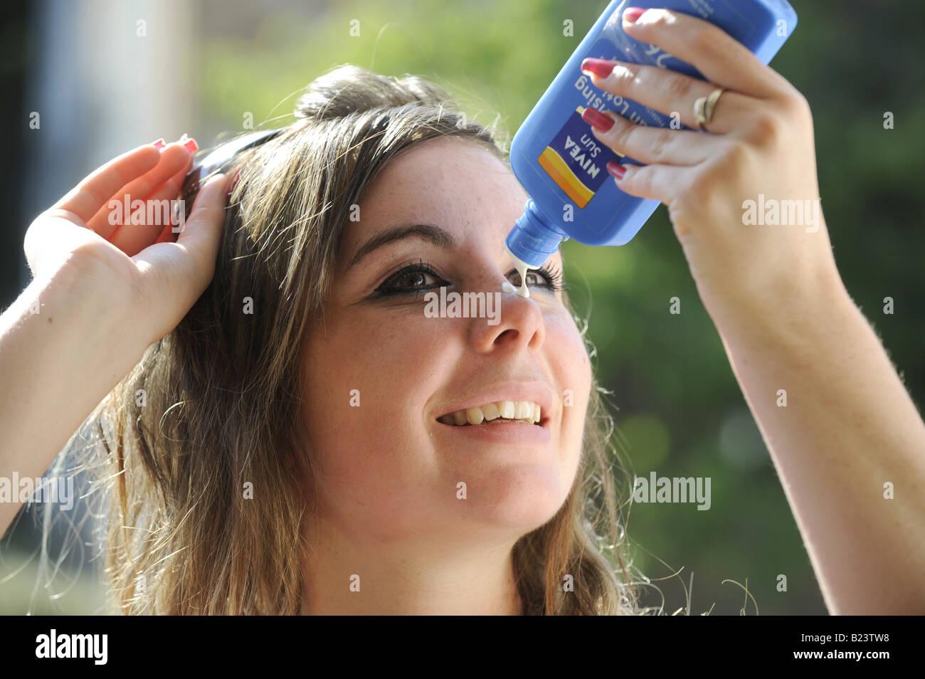 Teenage girl applying sun tan lotion to her face - Stock Image