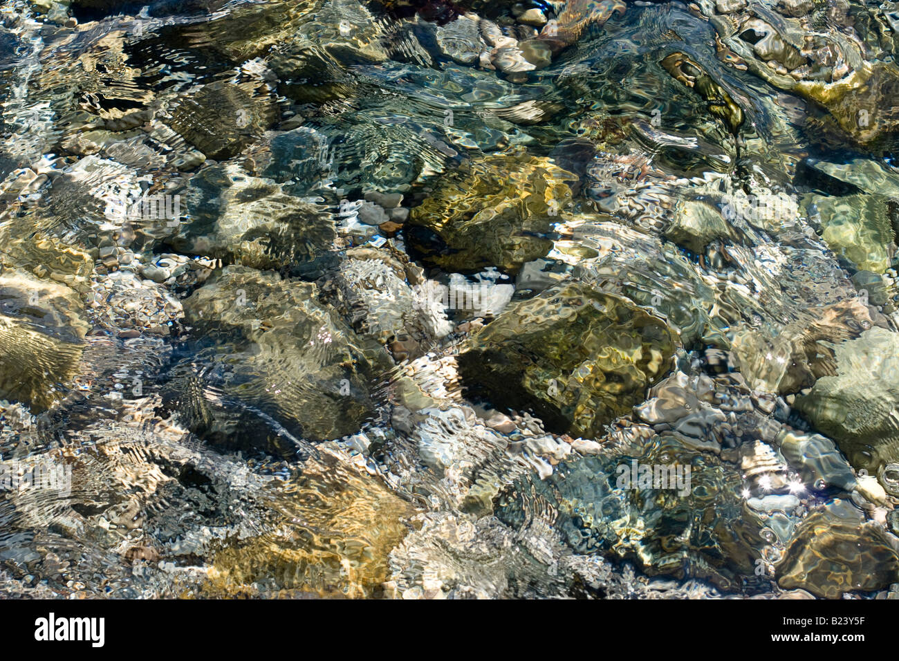 Stony sea floor viewed through gentle waves - Stock Image