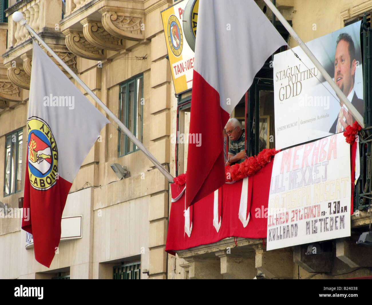 Flags and posters flanking the adorned balcony of the Maltese Labour Party premises in Valletta, Malta. - Stock Image