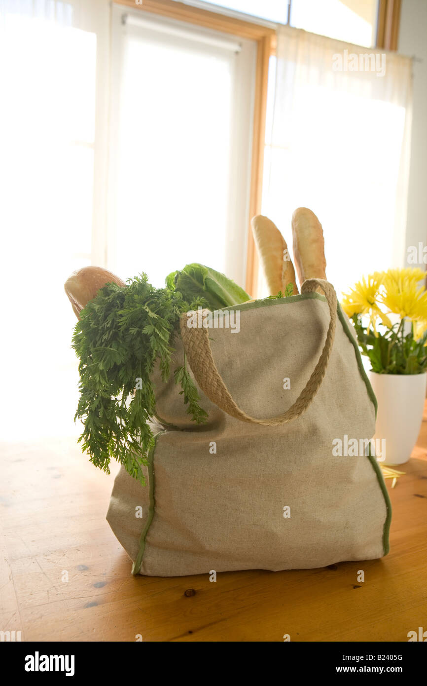 reusable grocery bag full of food on table with bright window light - Stock Image