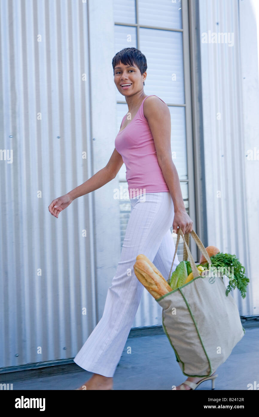 green shopping bag full of groceries carried by African American woman walking. - Stock Image