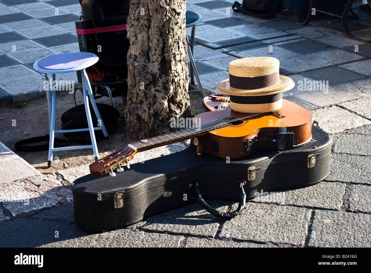 Street musician s guitar case and straw hats on a street in Taormina, Sicily, Italy - Stock Image