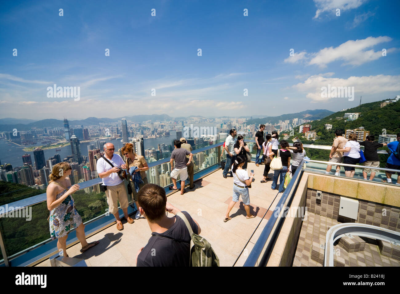 Tourists taking pictures and looking at Hong Kong Panorama from the viewing terrace of the Victoria Peak Tower on - Stock Image