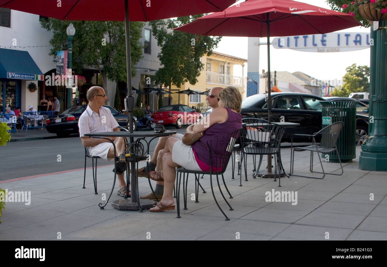 Three people sitting at a sidewalk table in Little Italy of San Diego. - Stock Image