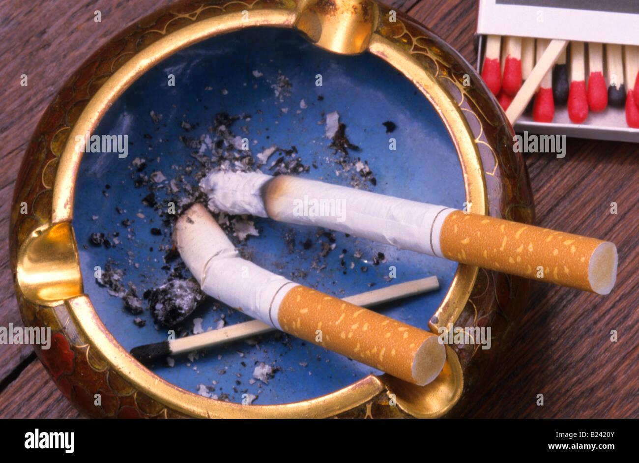 Two cigarettes burning in ashtray - Stock Image