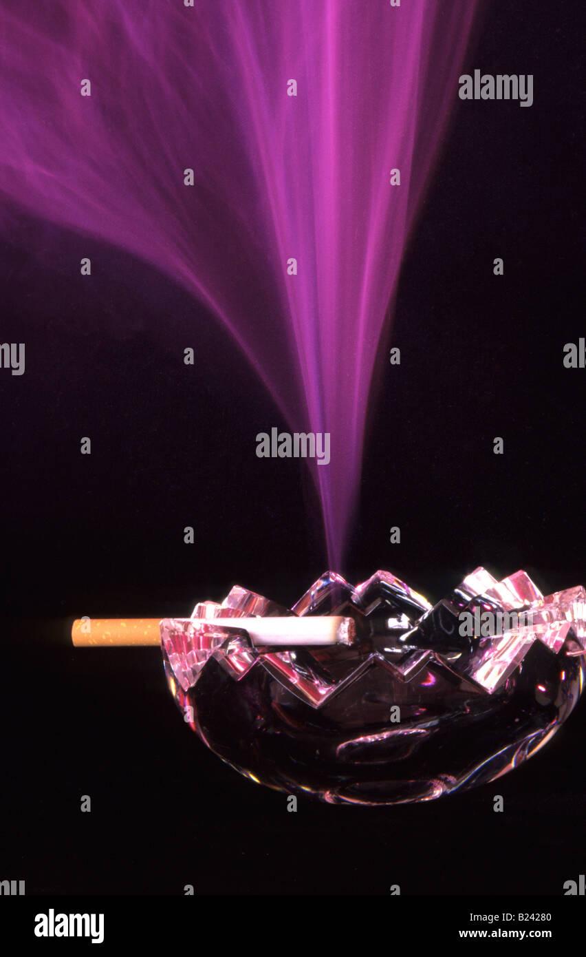 STILL LIFE CIGARETTE BURNING IN ASHTRAY - Stock Image