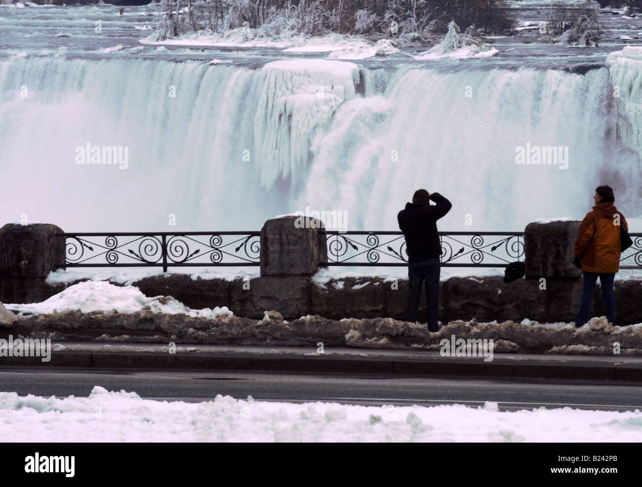 Tourists photographing American Falls of Niagara Falls in Winter - Stock Image