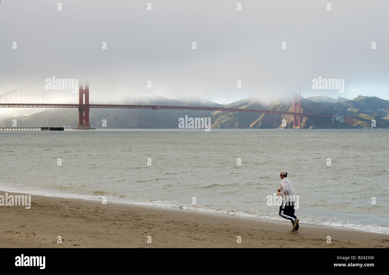 A lonely jogger running towards Golden Gate Bridge on the beach on a cold foggy San Francisco day Left foot is motion - Stock Image