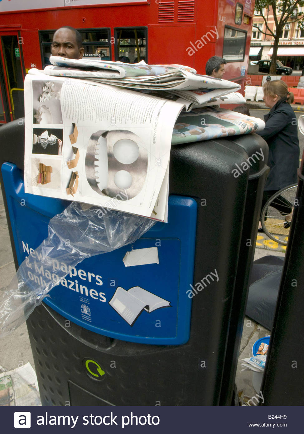 Newspapers to be recycled in Recycling Bins in Sloane Square London with London Buses passing - Stock Image