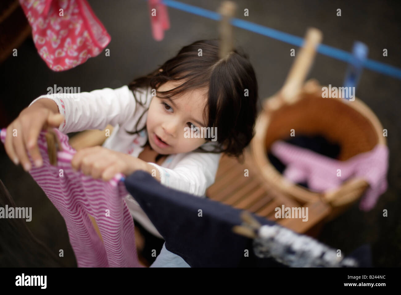 Hanging laundry on washing line to dry girl aged five and brother six - Stock Image