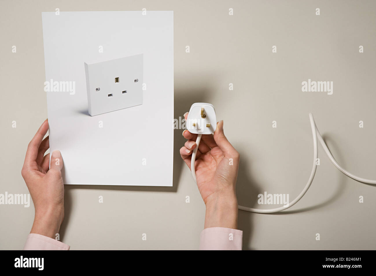 A woman holding a photograph of a socket and a plug Stock Photo