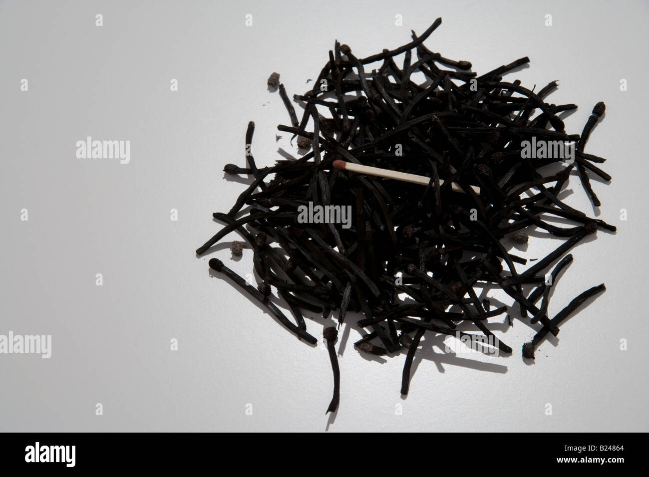New match on a stack of burnt matches - Stock Image
