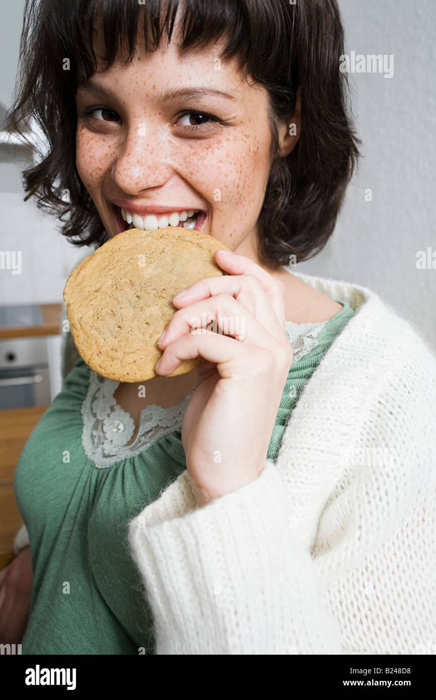 Freckled woman eating a biscuit - Stock Image