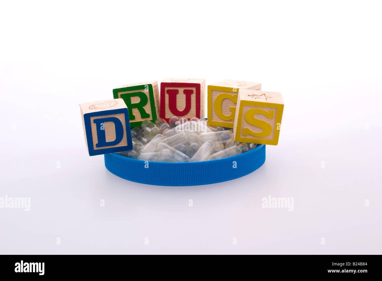 Children's blocks spellling 'drugs' with empty medicine capsules - Stock Image