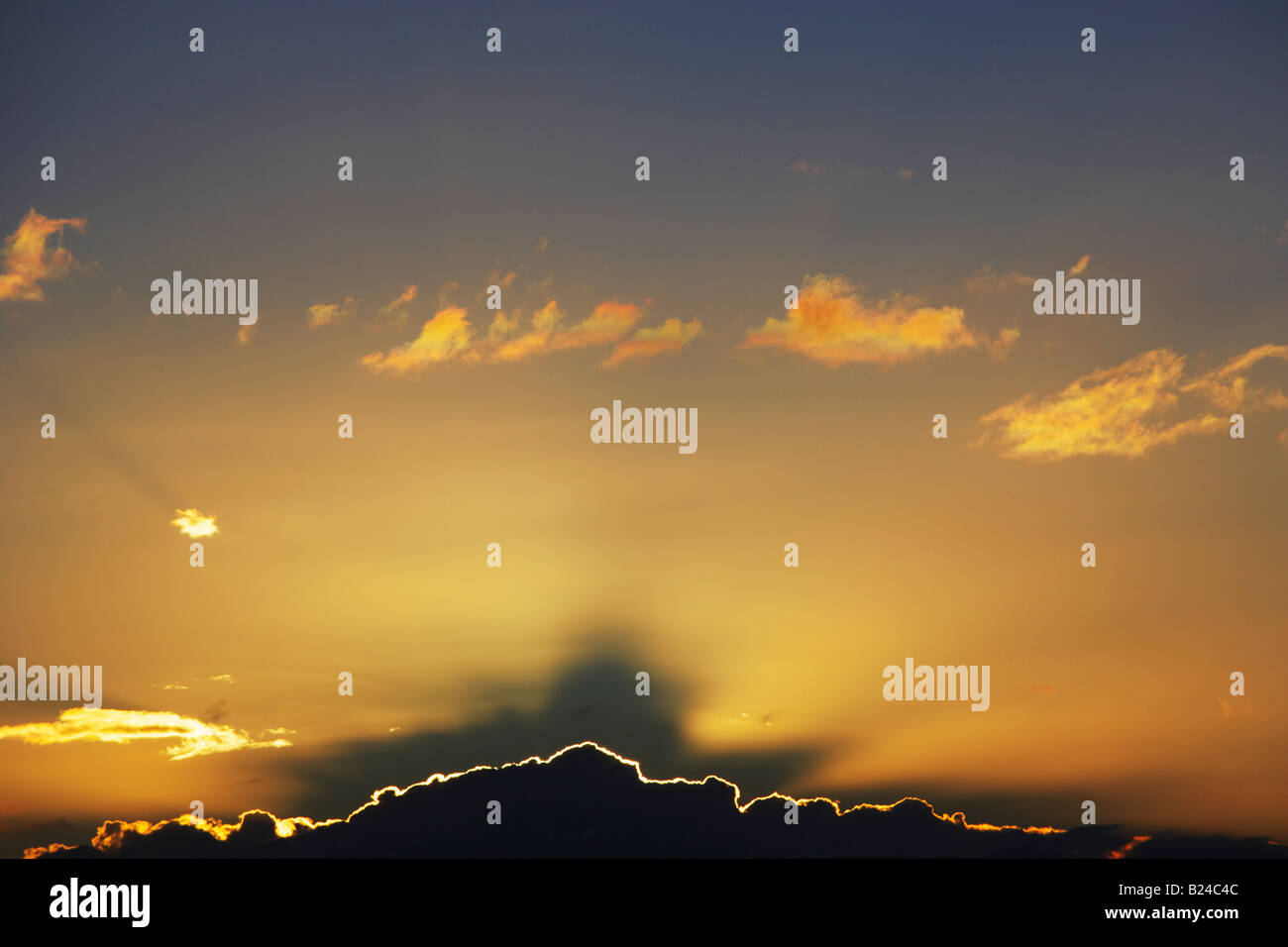 Sun going down behind large cloud causing silver lining and dramatic sky Sydney Australia - Stock Image