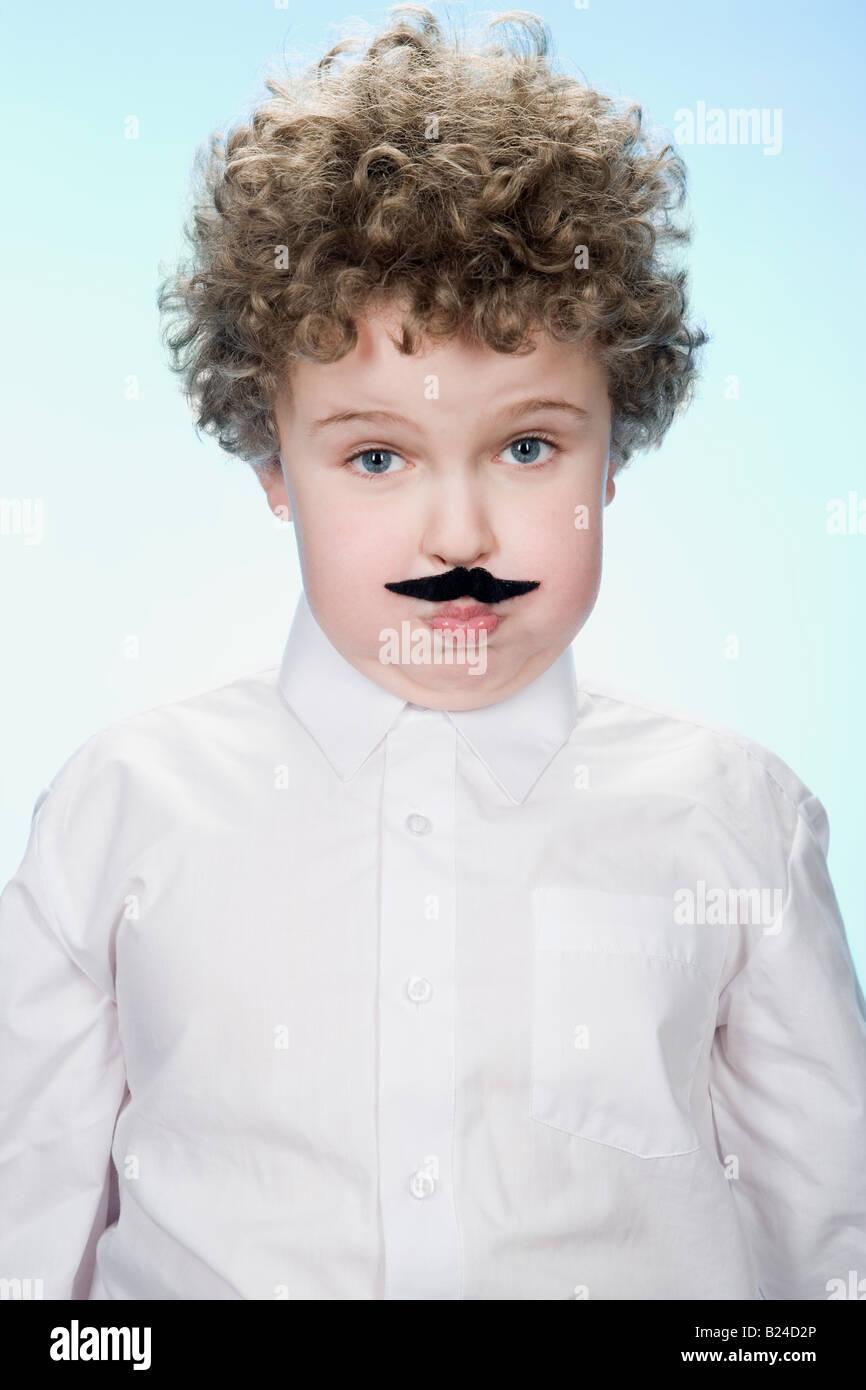 Portrait of a boy wearing a fake moustache - Stock Image