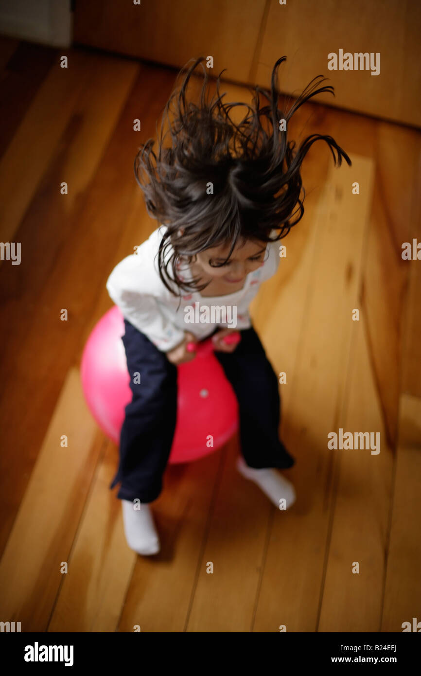Girl aged five bounces on pink moonhooper indoors - Stock Image