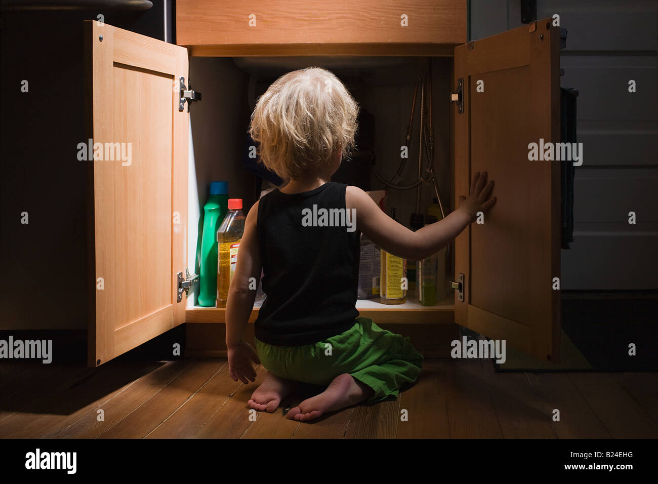 Little boy opening cupboard of cleaning products Stock Photo