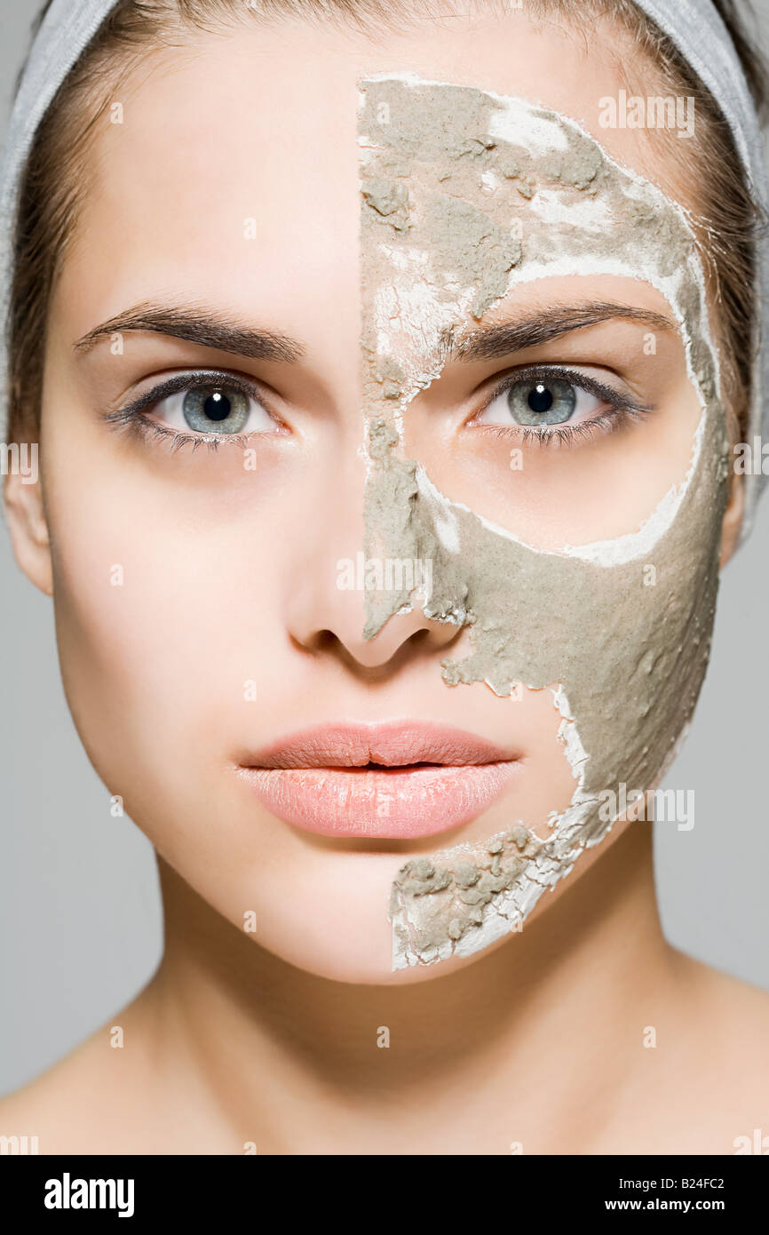 Woman with face mask on half of her face - Stock Image