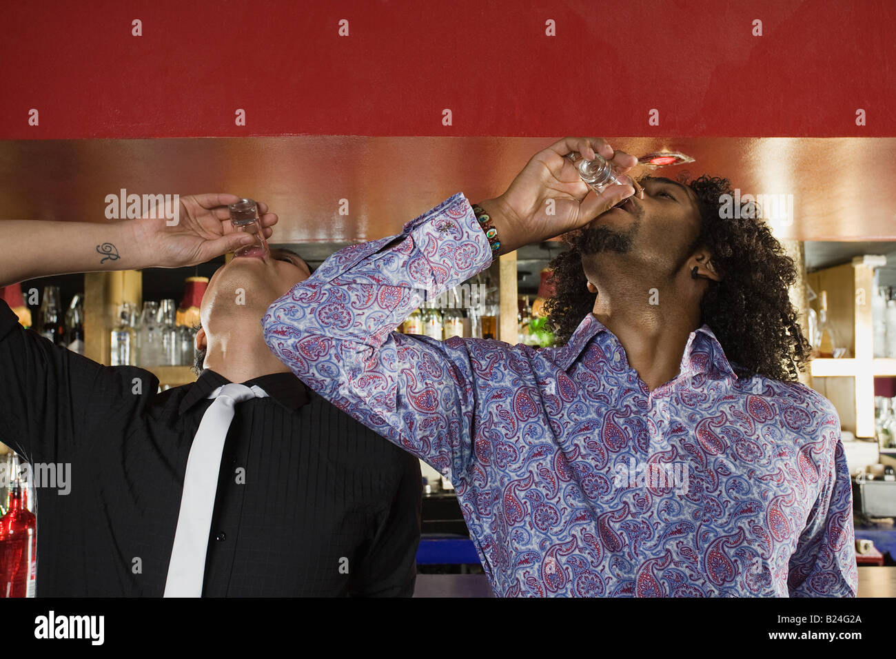 Friends downing shots - Stock Image