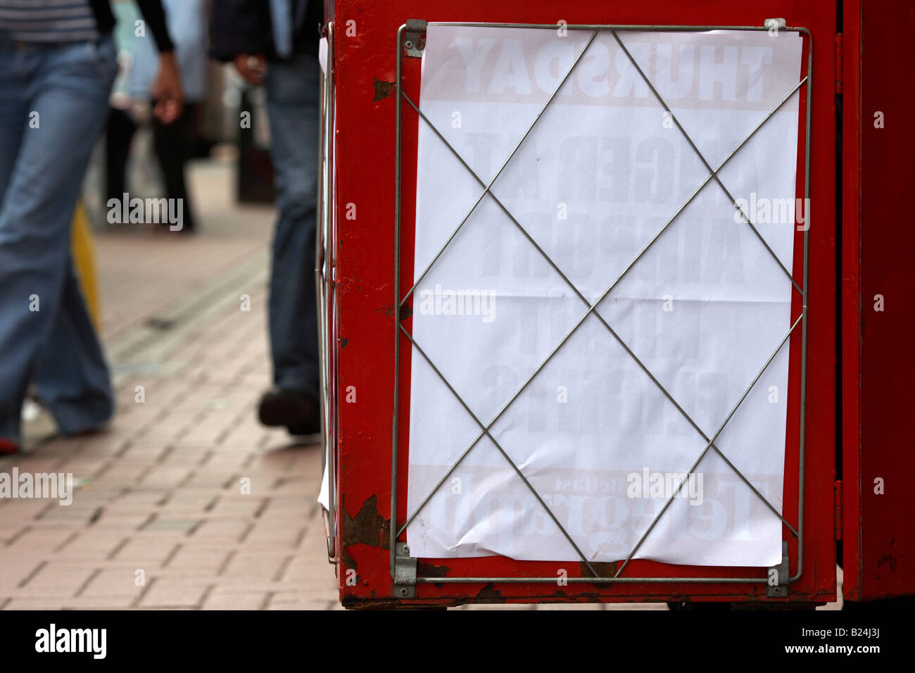 people walking past blank newspaper board in belfast city centre - Stock Image