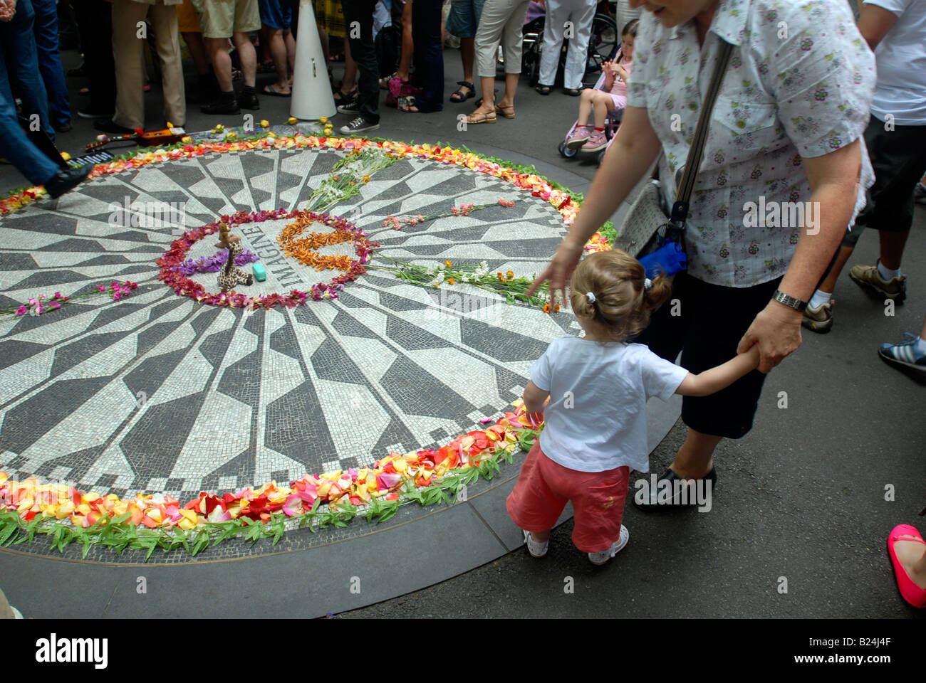 Visitors to the Imagine mosaic in Strawberry Fields memorializing John Lennon in Central Park in New York - Stock Image