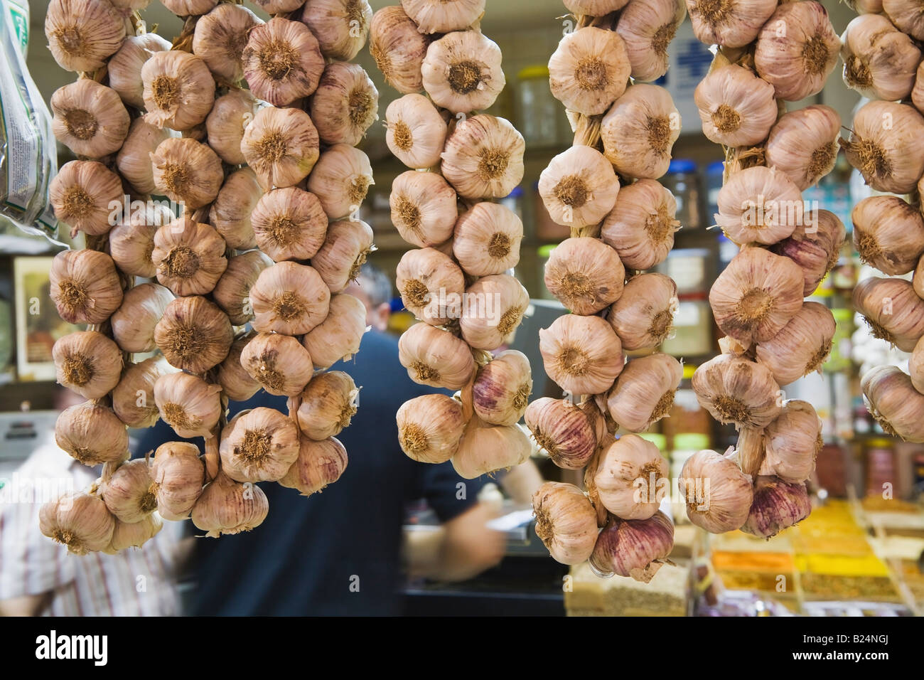 Strings of garlic in market Spain - Stock Image