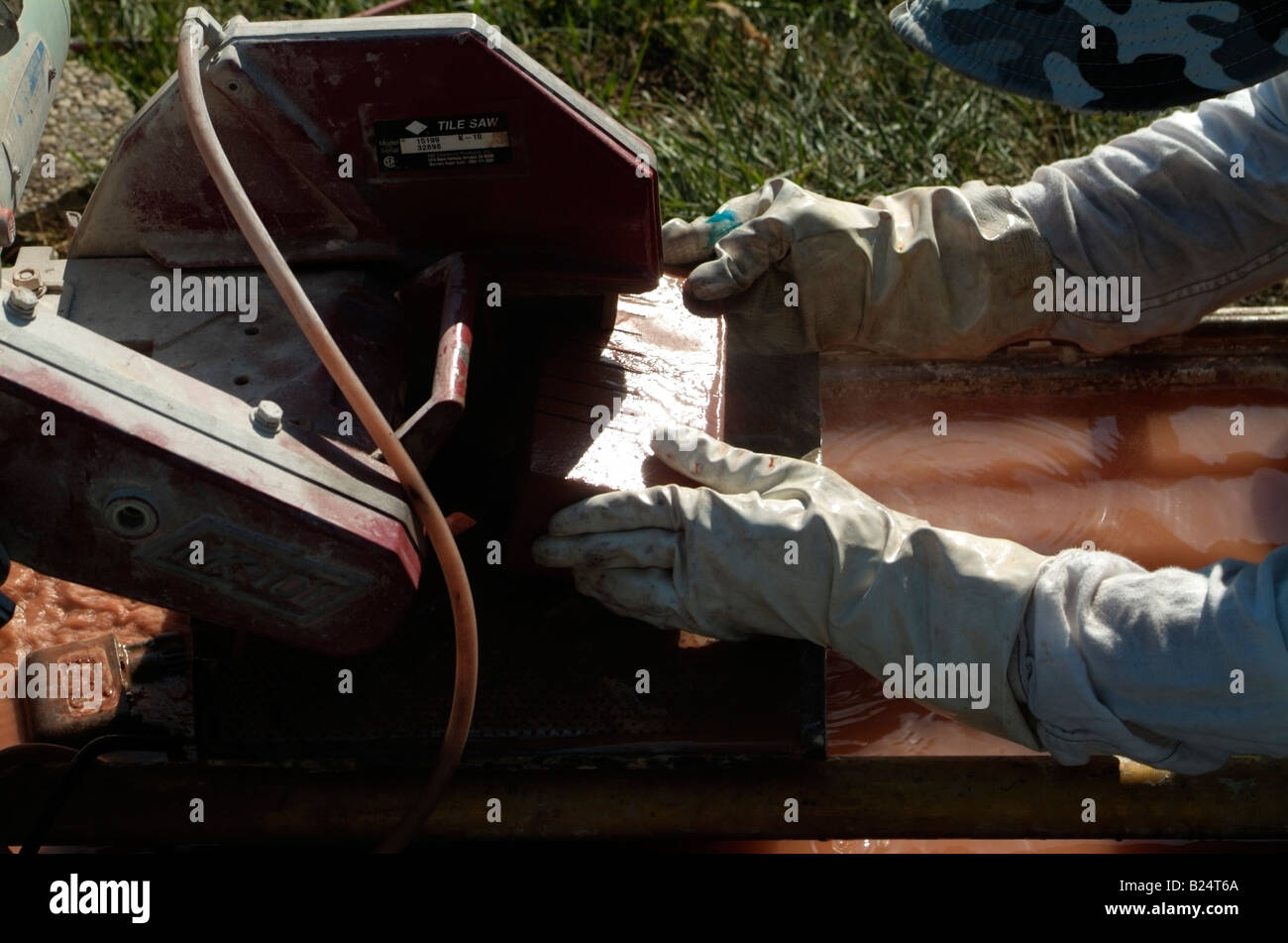 Stone Mason cuts a red clay brick with an Electic Tile Saw in San Jose, CA. Stock Photo