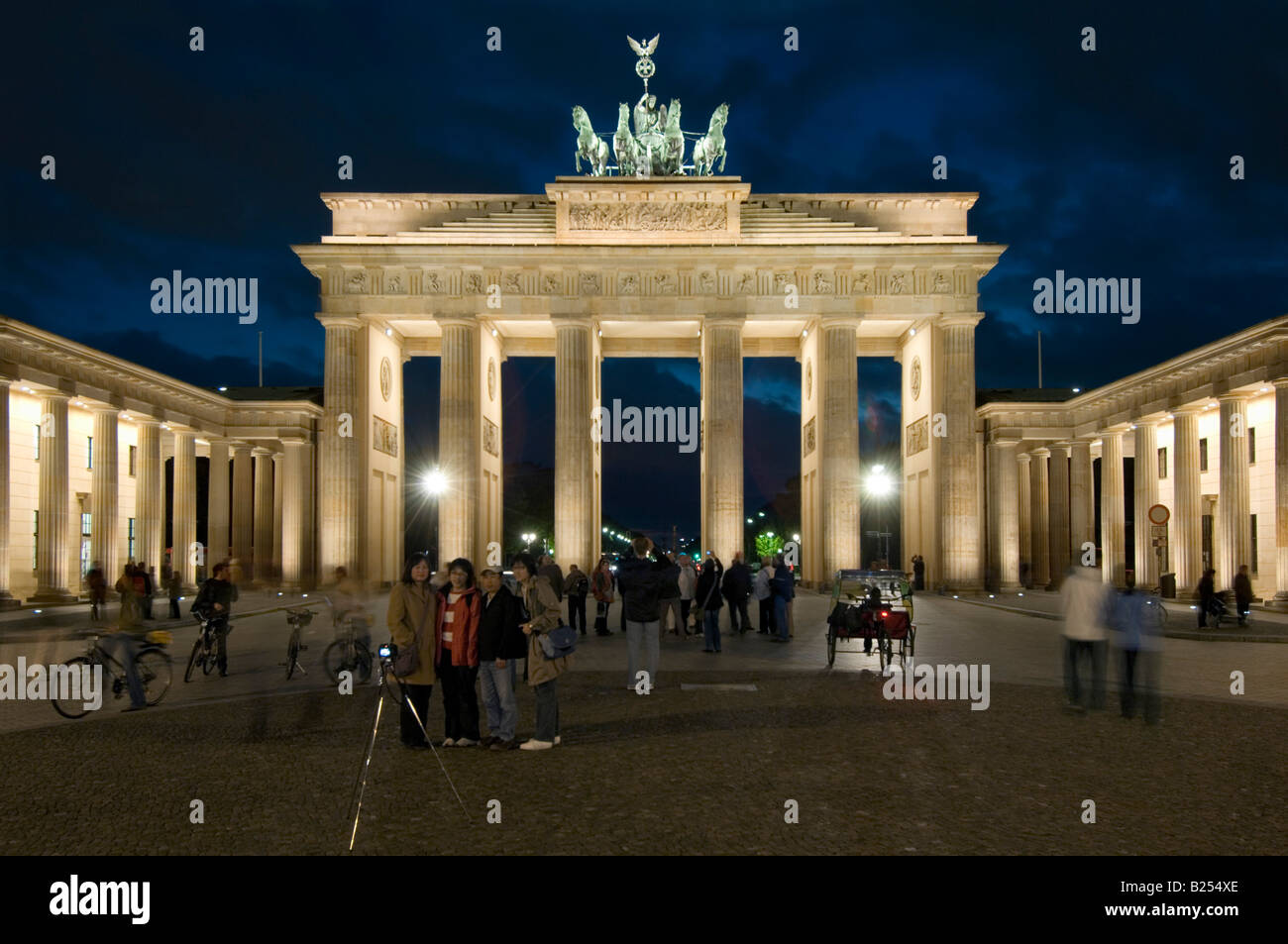 A view of tourists taking photographs at the Brandenburger Tor or Brandenburg Gate at dusk evening. - Stock Image